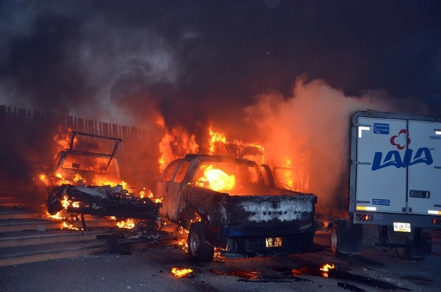Vehicles set to fire by rural college students, burn outside the entrance of the Governor's Palace in Guerrero's state capital, Chilpancingo, Mexico, Saturday, Nov. 8, 2014. Suspects in the disapp ...