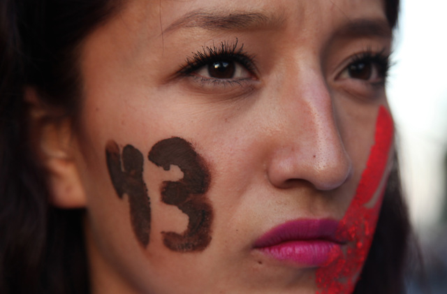 A female demonstrator with the number 43 painted on her face marches in protest for the disappearance of 43 students in the state of Guerrero, in Mexico City, Wednesday, Nov. 5, 2014. Federal poli ...