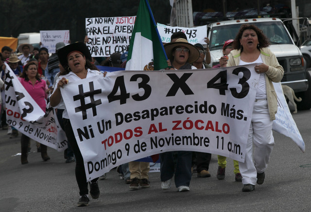 A group of 43 marchers, each representing one of the disappeared rural college students, parade through the streets, calling for people to gather at the city's main plaza, in Mexico City, Saturday ...