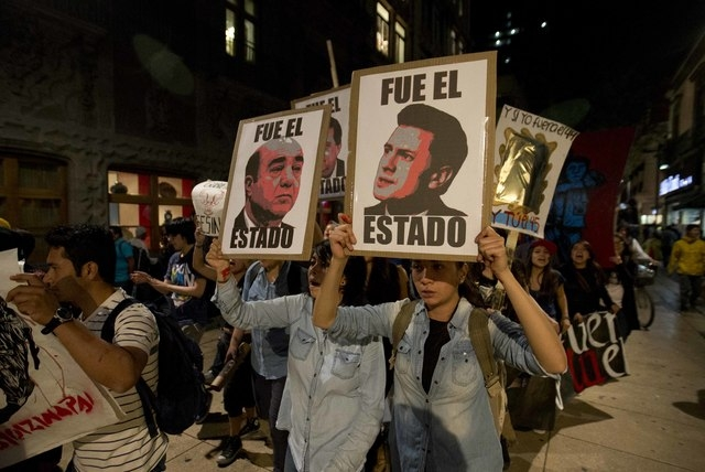 Demonstrators holding posters of Mexico's President Enrique Pena Nieto, right, and Attorney General, Jesus Murillo Karam, left, march in protest for the disappearance of 43 students in the state o ...