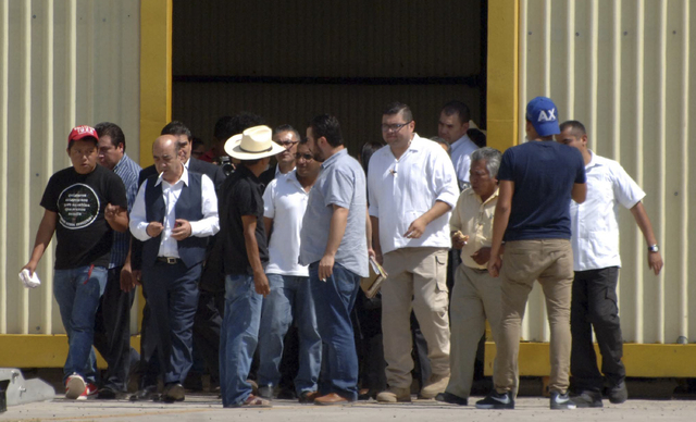 Mexico's Attorney General, Jesus Murillo Karam, third from left wearing a vest, leaves a hangar after meeting with relatives of the 43 missing students, at the airport in the state capital city of ...