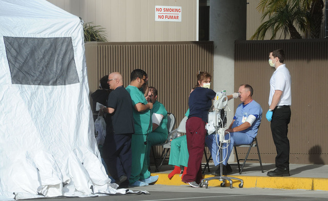Medical personnel at the Ventura County Medical Center, Tuesday, Nov. 18, 2014, in Ventura, Calif., decontaminate emergency personnel who came into contact with the injured people at a chemical ex ...