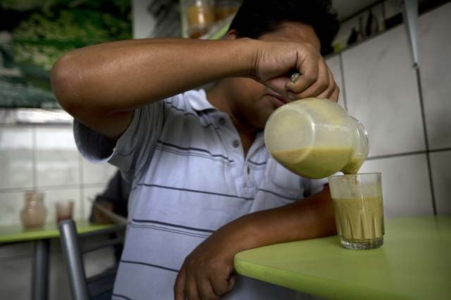 Customer Rudy Tolentino Casas serves frog juice at a juice bar in Lima, Peru, Monday, Nov. 17, 2014. To make the mix, which is sold in Perus Andes and also at some stands in its capital Lima, vend ...
