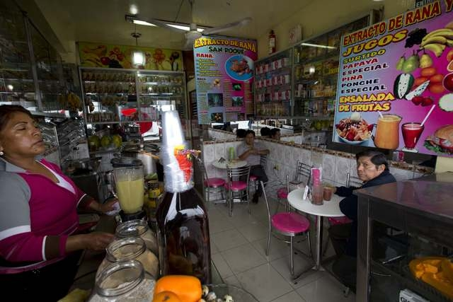 A juice bar advertises frog juice on the wall in Lima, Peru, Monday, Nov. 17, 2014. Frogs from Peru's Lake Titicaca are the main ingredient in a juice blend that is revered by some Andean cultures ...