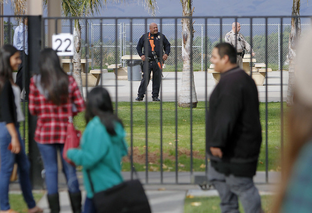 A Santa Maria Police Officer stands guard as Righetti High students leave the school after two fights broke out and the school was put on lockdown, Wednesday afternoon, Nov. 19, 2014 in Santa MAri ...
