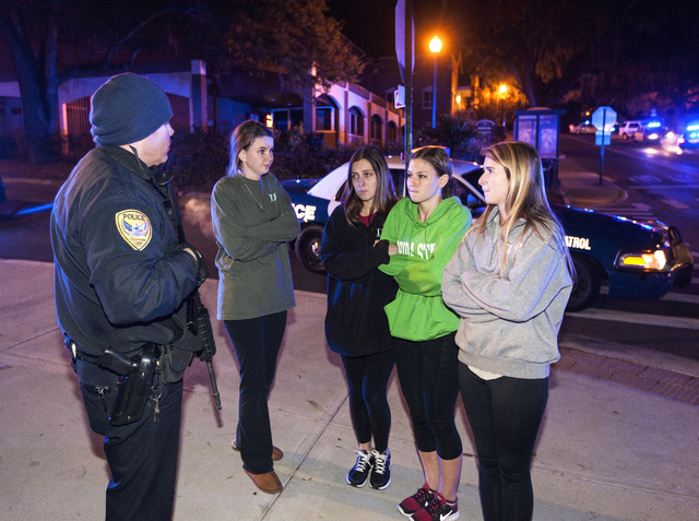 A Tallahassee police officer talks to several students outside the Strozier library on the Florida State University campus in Tallahassee, Fla., where a shooting occurred Thursday Nov 20, 2014. Th ...