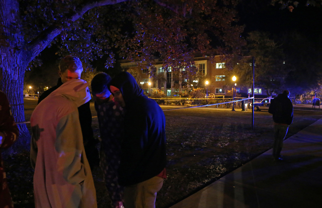 A group of students call their friends who were still locked down in Strozier Library on the Florida State University campus, background, after a shooting on Thursday, Nov. 20, 2014, in Tallahasse ...