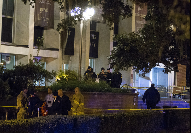 Tallahassee police investigate a shooting outside the Strozier library on the Florida State University campus in Tallahassee, Fla., Thursday Nov 20, 2014. Officers shot and killed the suspected gu ...
