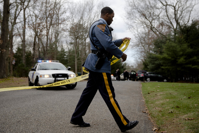 A New Jersey State Police Trooper secures a police line at the scene of a shooting Thursday, Nov. 20, 2014, in Tabernacle, N.J. New Jersey State Police say two people are dead and two were found w ...
