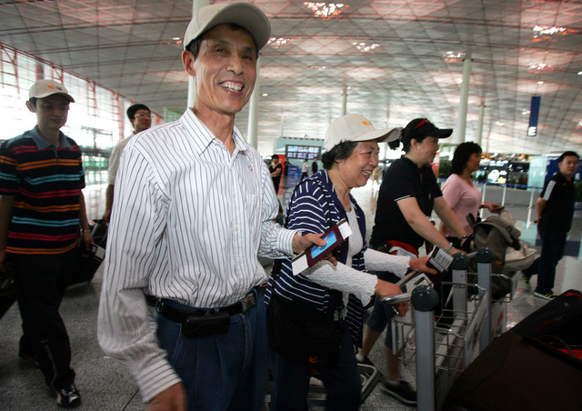 In this June 17, 2008, file photo, a group of Chinese tourists prepare to check-in on a United Airlines flight to Washington, at Beijing Capital International Airport. Chinese tourists, already am ...