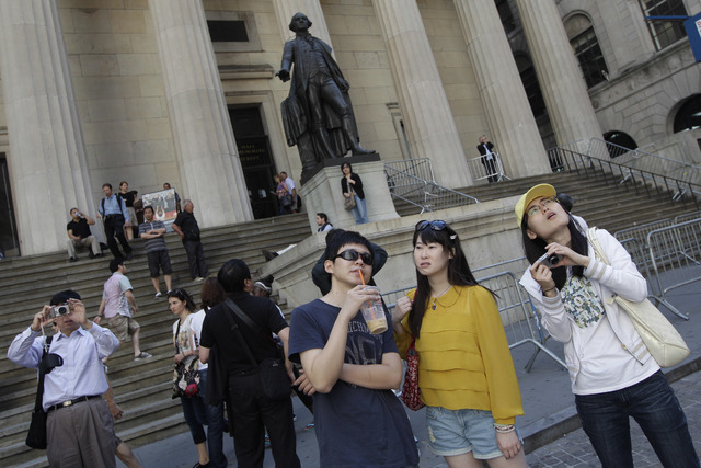 In this June 15, 2012, file photo, a group of tourists from China take in the sights of the New York Stock Exchange and Federal Hall National Memorial, in New York. Chinese tourists, already among ...