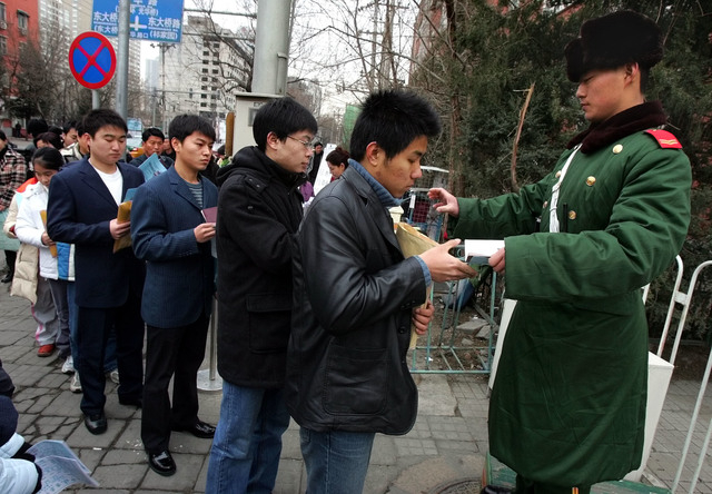In this March 3, 2005, file photo, a Chinese paramilitary police guard checks the documents of visa seekers outside the U.S. embassy in Beijing before letting them in. Chinese tourists, already am ...