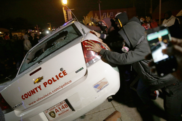 A group of protesters vandalize a police vehicle after the announcement of the grand jury decision not to indict police officer Darren Wilson in the fatal shooting of Michael Brown, an unarmed bla ...