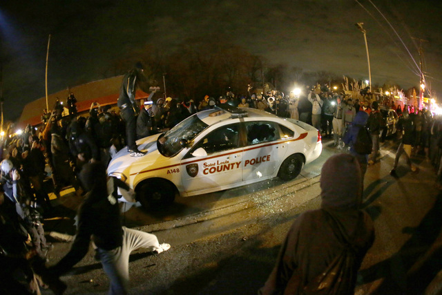 A protester squirts lighter fluid on a police car as the car windows are shuttered near the Ferguson Police Department after the announcement of the grand jury decision not to indict police office ...