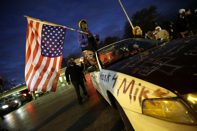 Gina Gowdy holds an upside-down American flag Monday, Nov. 24, 2014, in Ferguson, Mo., more than three months after an unarmed black 18-year-old man was shot and killed there by a white policeman. ...