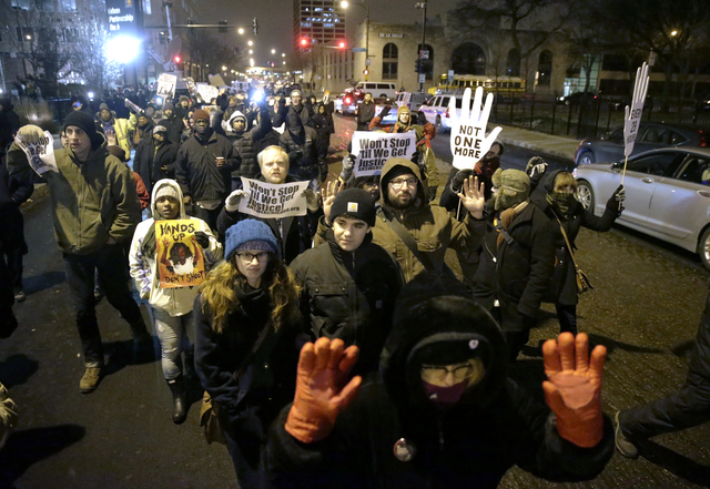 Protesters march during a rally near the Chicago Police headquarters after the announcement of the grand jury decision not to indict Ferguson police officer Darren Wilson in the fatal shooting of  ...