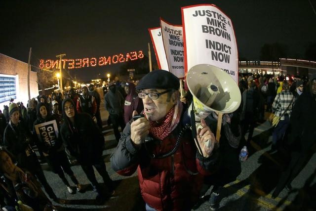Protesters gather in front of the Ferguson Police Department before the announcement of the grand jury decision about whether to indict a Ferguson police officer in the shooting death of Michael B ...