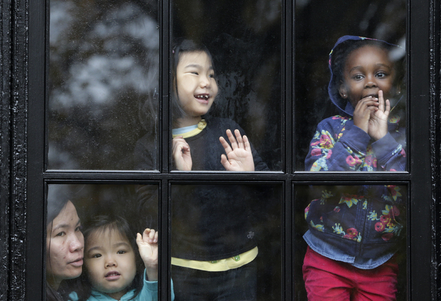 Children look out a window while trying to get a glimpse of balloons during the Macy's Thanksgiving Day Parade, Thursday, Nov. 27, 2014, in New York. (AP Photo/Julio Cortez)