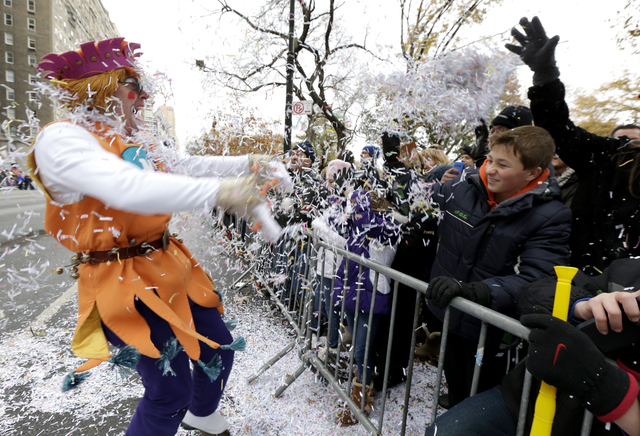 A performer, left, throws confetti on a crowd during the Macy's Thanksgiving Day Parade, Thursday, Nov. 27, 2014, in New York. (AP Photo/Julio Cortez)