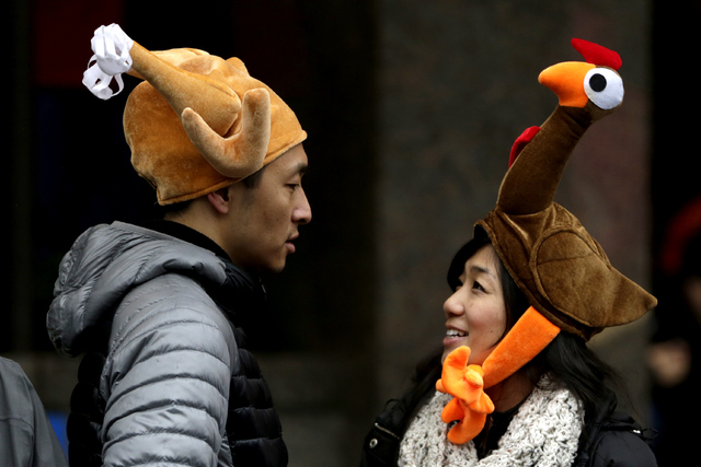 Tamari Hedani, right, and her boyfriend, Chris Chu, both from San Francisco, wear turkey hats prior to the start of the Macy's Thanksgiving Day Parade, Thursday, Nov. 27, 2014, in New York. (AP Ph ...