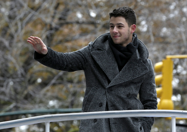 Singer Nick Jonas waves at the crowd during the Macy's Thanksgiving Day Parade, Thursday, Nov. 27, 2014, in New York. (AP Photo/Julio Cortez)