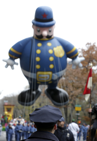 A New York City police officer stands guard as a balloon in the shape of a police officer makes its way during the Macy's Thanksgiving Day Parade, Thursday, Nov. 27, 2014, in New York. (AP Photo/J ...