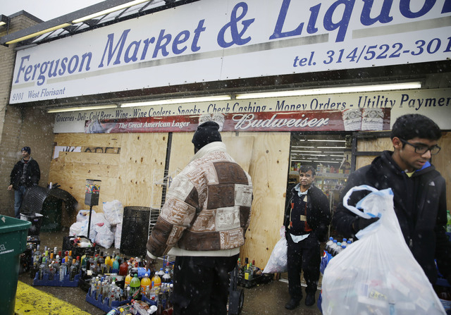 Kush Patel, right, carries out bags of merchandise while helping his uncle Andy Patel, rear, clean up the looting damage from Monday's riots at his store, Ferguson Market and Liquor, Wednesday, No ...