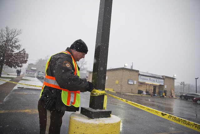 A police officer tightens tape sealing off an area to the public at the scene of Monday's riots that damaged numerous businesses, Wednesday, Nov. 26, 2014, in Ferguson, Mo.  A grand jury's decisio ...