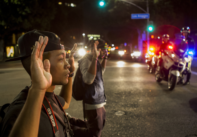Protesters kneel down with their hands up in front of Los Angeles police officers in downtown Los Angeles on Wednesday, Nov. 26, 2014. People protesting the Ferguson, Mo., grand jury decision took ...