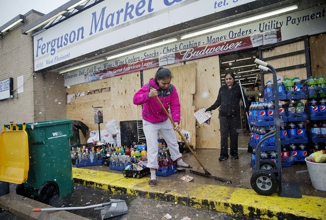 Anjana Patel cleans up the damage from Monday's riots at her store, Ferguson Market and Liquor, Wednesday, Nov. 26, 2014, in Ferguson, Mo.  A grand jury's decision not to indict a police officer i ...