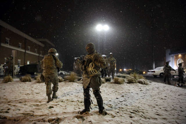 Snow falls as Missouri National Guard stand outside of the Ferguson Police Department Wednesday, Nov. 26, 2014, in Ferguson, Mo. A grand jury's decision not to indict a police officer in the shoot ...