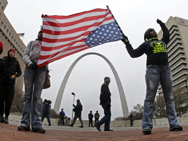 Protesters stand in front of the Gateway Arch as they demonstrate in downtown St. Louis Wednesday, Nov. 26, 2014. Since a grand jury's decision was announced Monday night, Nov. 24, not to indict a ...