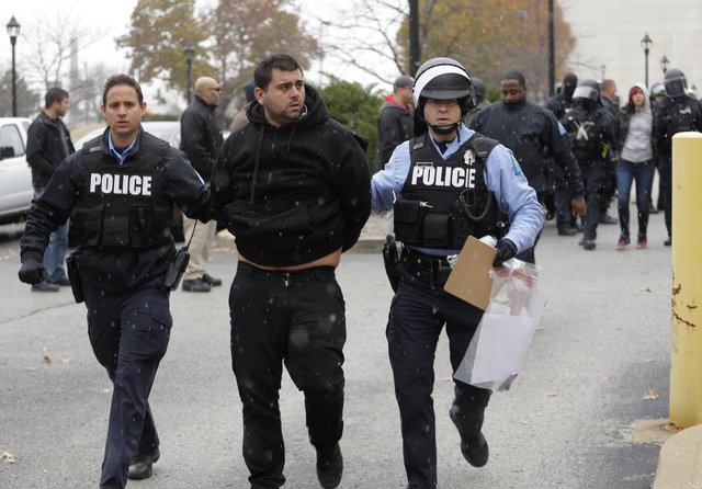 A protester is arrested outside of City Hall Wednesday, Nov. 26, 2014, in St. Louis. Several people protesting the Ferguson grand jury decision stormed into City Hall in St. Louis on Wednesday, le ...