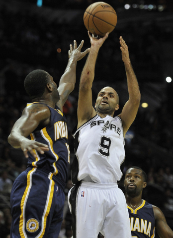 San Antonio Spurs guard Tony Parker, right, of France, shoots against Indiana Pacers guard Donald Sloan during the first half of an NBA basketball game, Wednesday, Nov. 26, 2014, in San Antonio. ( ...
