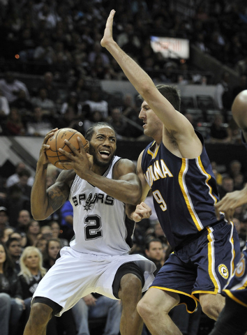 San Antonio Spurs forward Kawhi Leonard, left, drives around Indiana Pacers forward Damjan Rudez, of Croatia, during the first half of an NBA basketball game, Wednesday, Nov. 26, 2014, in San Anto ...