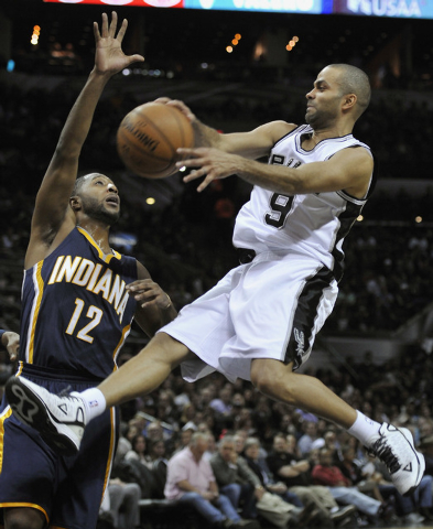 San Antonio Spurs guard Tony Parker, right, of France, passes around Indiana Pacers guard A.J. Price during the first half of an NBA basketball game, Wednesday, Nov. 26, 2014, in San Antonio. (AP  ...