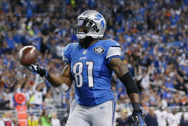 Detroit Lions wide receiver Calvin Johnson tosses the ball after his 25-yard reception for a touchdown during the first half of an NFL football game against the Chicago Bears in Detroit, Thursday, ...