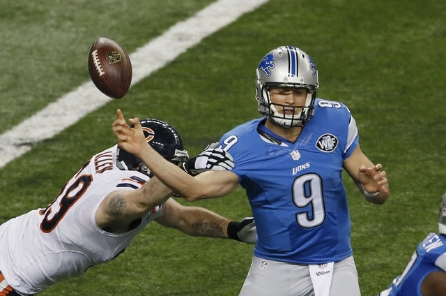 Chicago Bears defensive end Jared Allen (69) knocks the ball away from Detroit Lions quarterback Matthew Stafford (9) during the first half of an NFL football game in Detroit, Thursday, Nov. 27, 2 ...