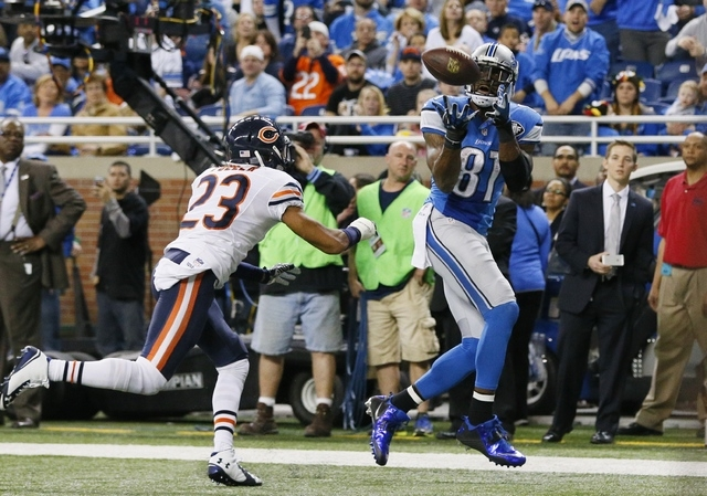 Detroit Lions wide receiver Calvin Johnson (81), defended by Chicago Bears cornerback Kyle Fuller (23), pulls in a 6-yard pass for a touchdown during the first half of an NFL football game in Detr ...