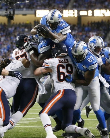 Detroit Lions running back Joique Bell jumps over the Chicago Bears defense for a 1-yard touchdown during the first half of an NFL football game in Detroit, Thursday, Nov. 27, 2014. (AP Photo/Rick ...