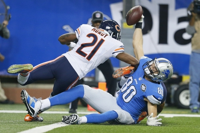 Detroit Lions tight end Joseph Fauria (80), defended by Chicago Bears strong safety Ryan Mundy (21) holds up the ball after his 8-yard reception during the second half of an NFL football game in D ...