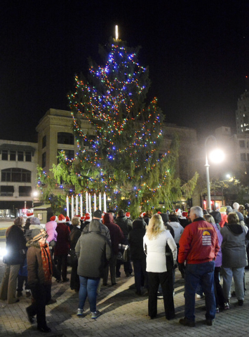 In this photo taken on Friday, Nov. 21, 2014, residents look on duing the Christmass the tree lighting in Reading, Pa. Reading's spindly 50-foot spruce drew the ire of residents who said it was ru ...