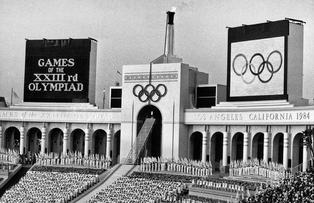 The Olympic flame is flanked by a scoreboard signifying the formal opening of the XXIII Olympiad after it was lit by Rafer Johnson during the opening ceremonies in the Los Angeles Memorial Coliseu ...