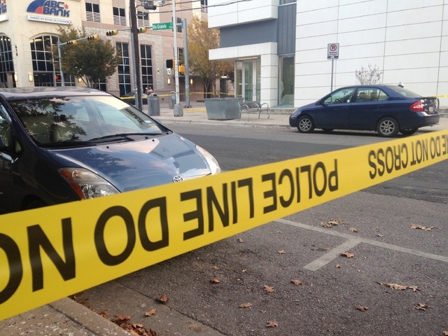 Police tape marks off the scene after authorities shot and killed a man who they say opened fire on the Mexican Consulate, police headquarters and other downtown buildings early Friday, Nov. 28, 2 ...