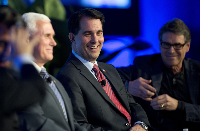 FILE - This Nov. 19, 2014, file photo shows Wisconsin Gov. Scott Walker, joined by Indiana Gov. Mike Pence, left, and Texas Gov. Rick Perry, right, at the Republican Governors Association annual c ...