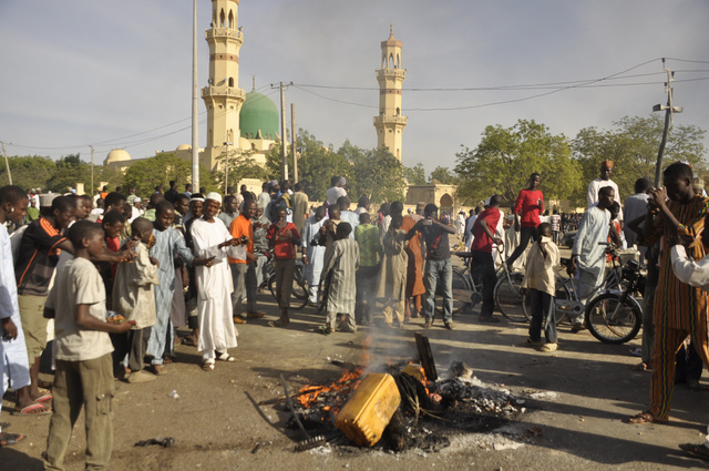 People gather at the site of a bomb explosion in Kano, Nigeria, Friday Nov. 28, 2014. An explosion tore through the central mosque in Nigeria's second-largest city on Friday, and officials feared  ...