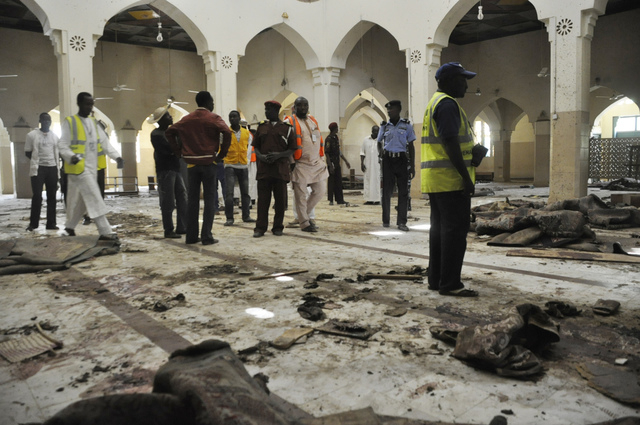 People inspect the central mosque following a bomb explosion in Kano, Nigeria, Saturday Nov. 29, 2014. More than 102 people were killed in the bomb explosions at the central mosque in Kano, said a ...