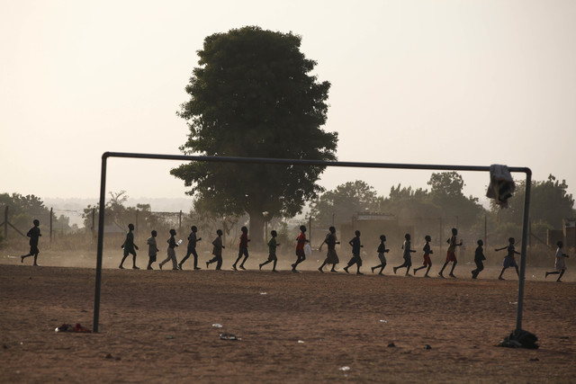 Internally displaced Children who fled their homes following an attack by Islamist militants in North East, Nigeria, run round a soccer ground at a camp in Yola, Nigeria, Friday Nov. 28, 2014.  So ...