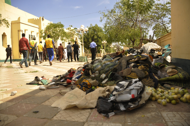 People walk past debris at the site of a bomb explosion in Kano, Nigeria Saturday Nov. 29, 2014.  More than 102 people were killed in the bomb explosions at the central mosque in Kano, said a hosp ...