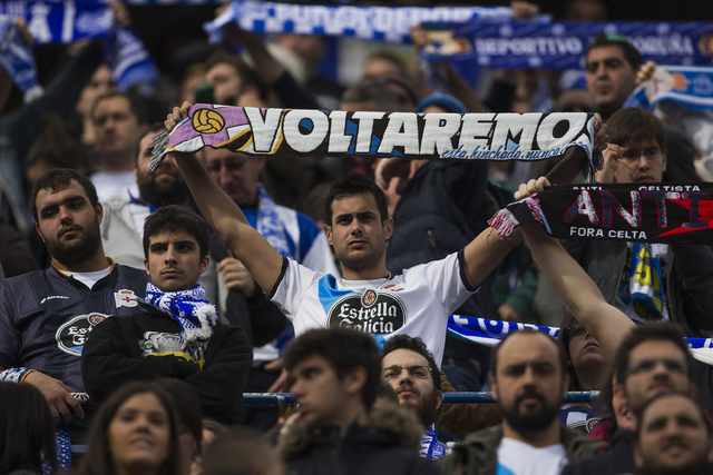 "Coruna's fan displays a scarf reading ""We will come back"" during a Spanish La Liga soccer match between Atletico and Deportivo Coruna at the Vicente Calderon stadium in Madrid, Spain, Sunday, Nov. ..."